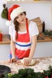Mujer morena joven que cocina la pizza o las pastas hechas a mano mientras que lleva el casquillo de Santa Claus en la cocina Pre Fotografía de archivo