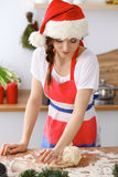Mujer morena joven que cocina la pizza o las pastas hechas a mano mientras que lleva el casquillo de Santa Claus en la cocina Pre Imágenes de archivo libres de regalías