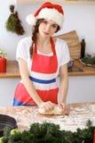 Mujer morena joven que cocina la pizza o las pastas hechas a mano mientras que lleva el casquillo de Santa Claus en la cocina Pre Foto de archivo