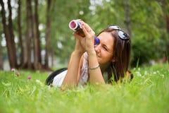 Mujer morena joven que disfruta de la mentira en la hierba verde Imagenes de archivo