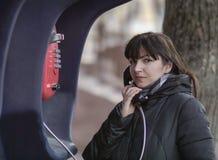 Mujer morena joven que llama de un teléfono público rojo de la calle, mirando directamente la cámara imagenes de archivo
