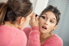 Mujer morena joven que pone maquillaje en el espejo imagenes de archivo