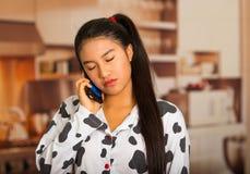 Mujer morena joven que presenta en los pijamas, hablando en el teléfono que parece cansado Imágenes de archivo libres de regalías