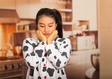 Mujer morena joven que presenta en pijamas y que hace frente a la cámara mientras que toca la cara usando las manos, pareciendo c Fotos de archivo libres de regalías