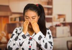 Mujer morena joven que presenta en pijamas y que limpia ojos usando las manos, pareciendo cansadas Imágenes de archivo libres de regalías