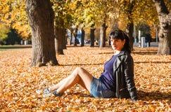 Mujer morena joven que se sienta en la hierba fotos de archivo libres de regalías