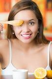 Mujer morena joven que se sienta sosteniendo el cuchillo de madera con el goteo de oro de la miel de él, sonriendo feliz Foto de archivo libre de regalías