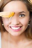 Mujer morena joven que se sienta sosteniendo el cuchillo de madera con el goteo de oro de la miel de él, sonriendo feliz Imagen de archivo