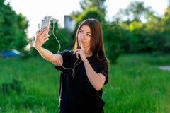 Mujer morena joven que sonríe feliz en verano en parque Comunica en redes sociales Manos que celebran su mostrar de los labios imagenes de archivo