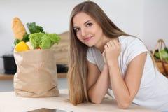 Mujer morena joven que sonríe mientras que se sienta en la tabla cerca de bolsa de papel por completo de verduras y de frutas Con fotos de archivo