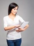 Mujer morena joven que sostiene una tableta en gris Imagenes de archivo