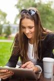 Mujer morena joven que usa la tableta digital al aire libre en un parque Fotografía de archivo