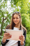 Mujer morena joven que usa la tableta digital al aire libre en un parque Imágenes de archivo libres de regalías