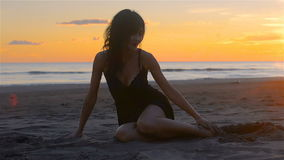 Mujer morena joven sensual que tiene playa arenosa de la diversión en la puesta del sol almacen de video