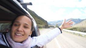 Mujer morena joven sonriente en un coche que juega con el viento y que conduce más allá de las montañas hermosas Imágenes de archivo libres de regalías