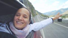 Mujer morena joven sonriente en un coche que juega con el viento y que conduce más allá de las montañas hermosas Imagen de archivo