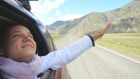 Mujer morena joven sonriente en un coche que juega con el viento y que conduce más allá de las montañas hermosas Fotos de archivo