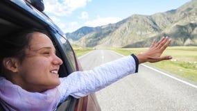 Mujer morena joven sonriente en un coche que juega con el viento y que conduce más allá de las montañas hermosas Imagenes de archivo