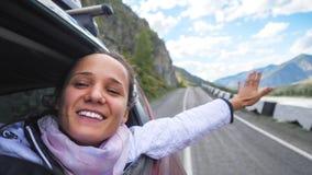 Mujer morena joven sonriente en un coche que juega con el viento y que conduce más allá de las montañas hermosas Imagen de archivo libre de regalías