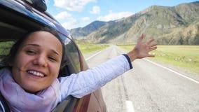 Mujer morena joven sonriente en un coche que juega con el viento y que conduce más allá de las montañas hermosas Foto de archivo