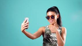 Mujer morena juguetona de la belleza en el vestido y los vidrios que plantean y que hacen el selfie en su smartphone almacen de video