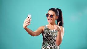 Mujer morena juguetona de la belleza en el vestido y los vidrios que plantean y que hacen el selfie en su smartphone almacen de metraje de vídeo