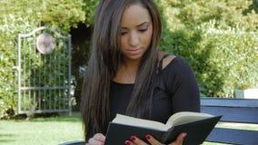 Mujer morena linda con un libro que presenta al aire libre almacen de metraje de vídeo