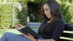 Mujer morena linda con un libro que presenta al aire libre almacen de video