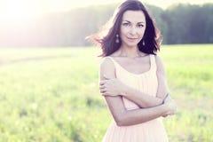 Mujer morena magnífica con actitud brillante del día de fiesta del concepto del estilo de la moda del sol de prado del verde del  Fotos de archivo libres de regalías