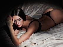 Mujer morena muy atractiva que presenta en ropa interior negra en cama Mujer caliente con el cuerpo delgado perfecto Fotos de archivo