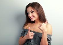 Mujer morena optimista feliz que muestra el pulgar encima de la muestra en vagos azules imagen de archivo
