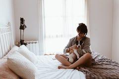 Mujer morena que abraza su perrito dulce de Labrador en dormitorio imagen de archivo libre de regalías
