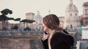 Mujer morena que camina en centro de ciudad, Roman Forum El hablar turístico femenino en el teléfono y sonrisa almacen de video