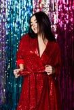 Mujer morena que celebra, divirti?ndose en la fiesta Retrato de una muchacha sonriente feliz en un vestido rojo brillante atracti foto de archivo