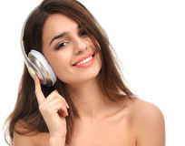 Mujer morena que escucha y que disfruta de música en auriculares del oro Imagenes de archivo