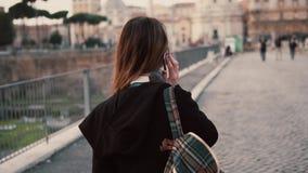 Mujer morena que habla en un teléfono durante caminar en Roman Forum La muchacha habla del viaje en Roma, Italia metrajes