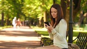 Mujer morena que manda un SMS en smartphone metrajes
