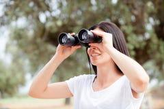Mujer morena que mira a través de los prismáticos Foto de archivo libre de regalías