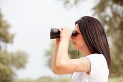 Mujer morena que mira a través de los prismáticos Imagenes de archivo
