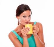 Mujer morena que pone mala cara con la taza de café Foto de archivo