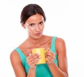 Mujer morena que pone mala cara con la taza de café Fotografía de archivo