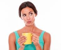 Mujer morena que pone mala cara con la taza de café Fotografía de archivo libre de regalías
