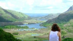 Mujer morena que se sienta en el top de una montaña que disfruta de la visión almacen de video