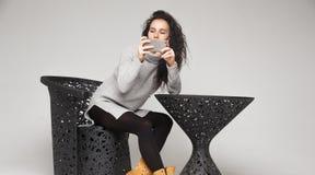 Mujer morena que se sienta en la tabla y que mira smartphone Foto de archivo