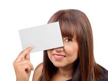 Mujer morena que se sostiene ocultando detrás de tarjeta en blanco aislada Imágenes de archivo libres de regalías