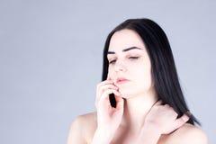 Mujer morena que toca su mejilla a mano y que mira abajo Concepto de la belleza Foto de archivo