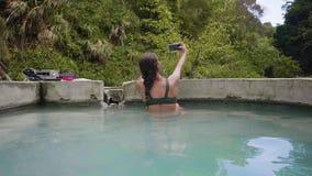 Mujer morena que toma el baño termal en la piscina de agua que presenta para el selfie del viaje en balneario natural El hacer de metrajes