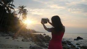 Mujer morena que toma una foto de la puesta del sol en su smartphone en la playa Cámara lenta 1920x1080 almacen de metraje de vídeo