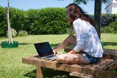 Mujer morena que usa el ordenador portátil en sillón Fotografía de archivo libre de regalías