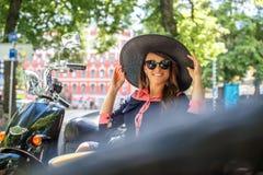 Mujer morena sonriente en sombrero negro grande del verano Foto de archivo